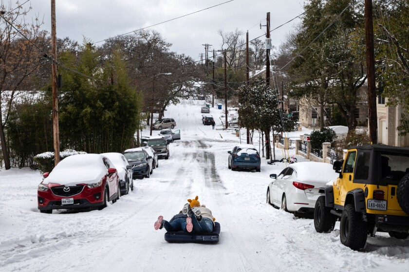 Two people use an air mattress to slide down a snow-covered street.
