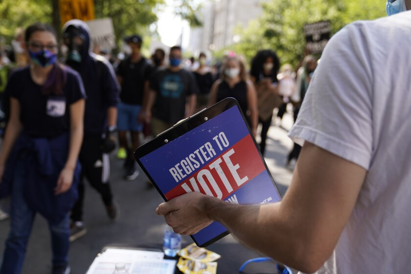 An activist holds a clipboard asking passersby to register to vote during a protest in Washington in June 2020.