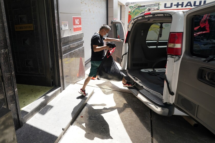 A man loads a bag onto a van at the Chinese Consulate in Houston.