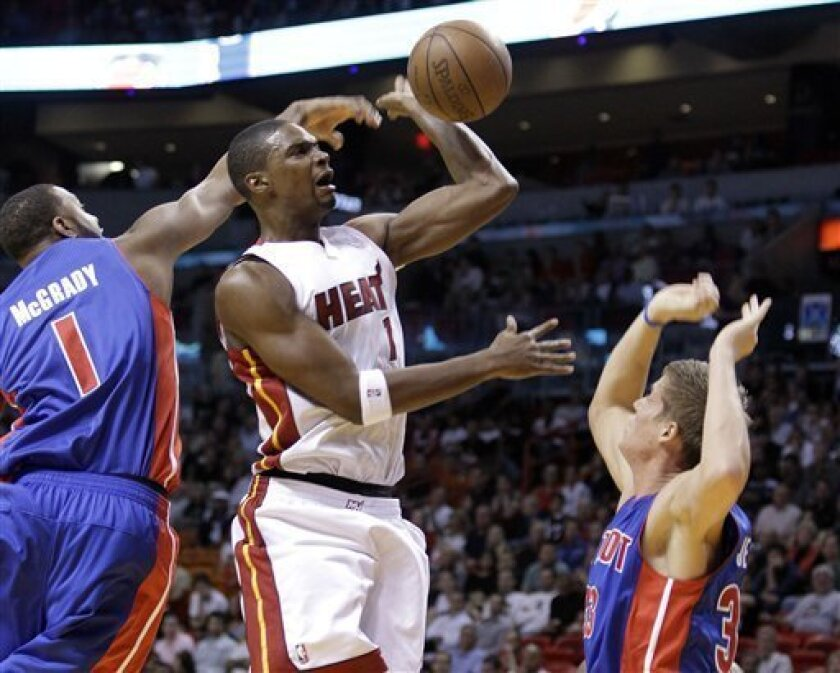 Miami Heat forward Chris Bosh, center, has his shot stopped by Detroit Pistons guard Tracy McGrady, left, as Detroit forward Jonas Jerebko, right, defends during the first quarter of a preseason NBA basketball game, Tuesday, Oct. 5, 2010, in Miami. (AP Photo/Lynne Sladky)