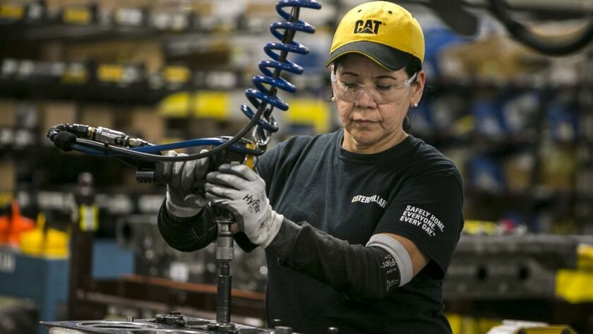 In this June 13, 2018, photo, Margarita Cardenas attaches an engine head at Caterpillar's engine man