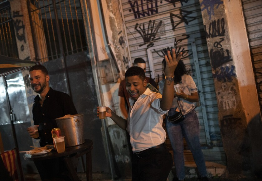 A man holding beer dances in the street