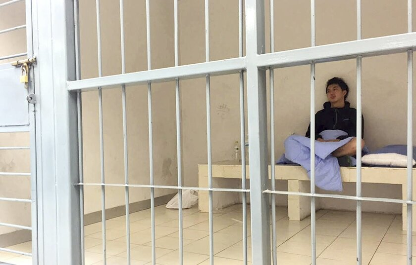 In his image provided by Initium Media Technology, Hong Kong journalist Hok Chun Anthony Kwan sits in a cell Monday, Aug. 24, 2015, after he was detained Sunday at Suvarnabhumi Airport in Bangkok, Thailand, for carrying body armor and a helmet onto a flight bound for Hong Kong. Kwan, who was in Bangkok covering the aftermath of last week's bombing, is being charged with possessing an illegal weapon, which carries a prison sentence of up to five years. (Initium Media Technology via AP)