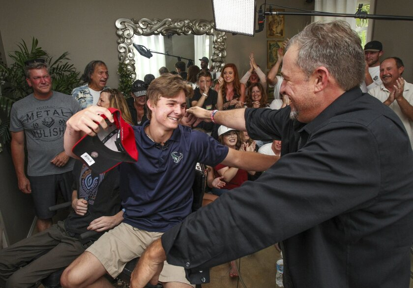 While live on MLB television, La Costa Canyon baseball player Mickey Moniak hugs his father Matt Moniak while family members and friends celebrate after it was announced that the Philadelphia Phillies picked Moniak as the number one MLB draft pick.