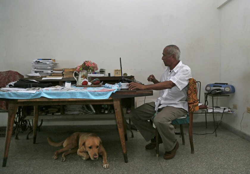 In this Thursday, April 16, 2015 photo, Cuban dissident Hildebrando Chaviano works at his laptop inside his home in Havana, Cuba. Chaviano, a government lawyer turned independent journalist, is one of at least two Cuban dissidents who made it past a first round of voting to become candidates in Sun