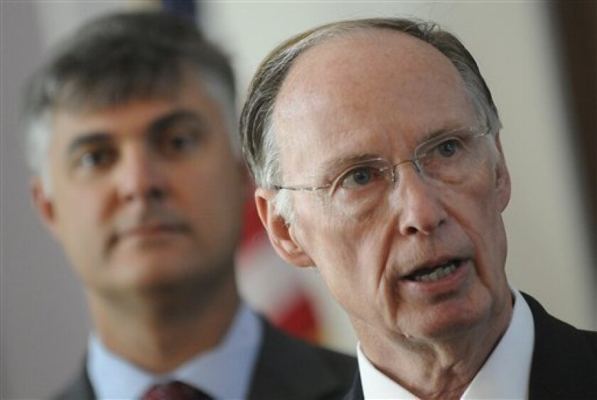 Sen. Scott Beason R-Gardendale, left, listens as Alabama Gov. Robert Bentley speaks before signing into law what critics and supporters are calling the strongest bill in the nation cracking down on illegal immigration, on Thursday June 9, 2011 at the state Capitol in Montgomery, Ala. The bill allows police to arrest anyone suspected of being an illegal immigrant if they're stopped for any other reason. It also requires public schools to determine students' immigration status and makes it a crime to knowingly give an illegal immigrant a ride. (AP Photo/Montgomery Advertiser, Mickey Welsh)