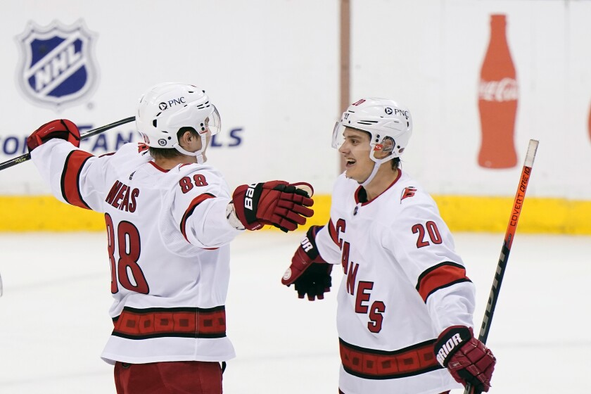 Carolina Hurricanes center Martin Necas (88) is congratulated by center Sebastian Aho (20) after Necas scored the winning goal during an overtime period of an NHL hockey game against the Florida Panthers, Monday, March 1, 2021, in Sunrise, Fla. (AP Photo/Wilfredo Lee)