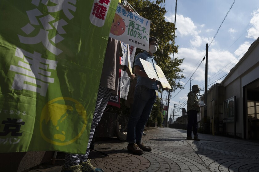 Miembros de Kodaira Solar sostienen carteles durante una manifestación para promover plantas de energía solar