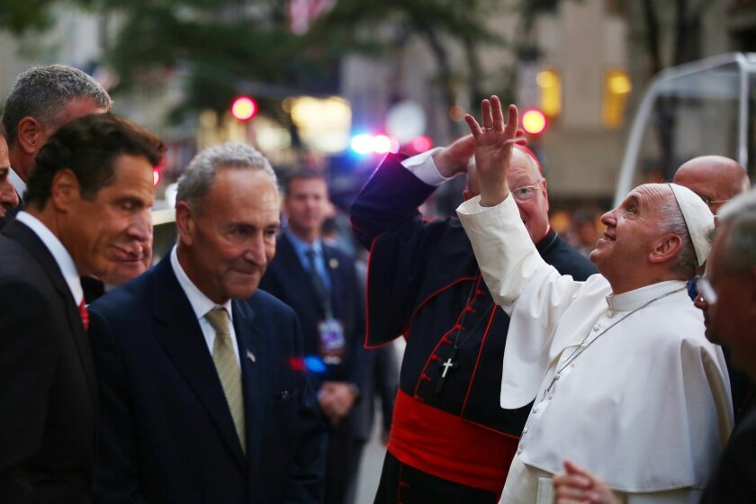 Pope Francis waves to the crowd as he arrives at St. Patrick's Cathedral, Thursday, Sept. 24, 2015, in New York. New York Gov. Andrew Cuomo, left, and Sen. Chuck Schumer, D-NY, wait to greet the pope. (Damon Winter/The New York Times via AP, Pool)