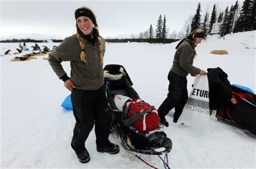 Kristy Berington, left, and twin sister Anna Berington, right, pack up their sleds as they prepare to leave the Finger Lake checkpoint in Alaska during the Iditarod Trail Sled Dog Race on Monday, March 4, 2013. (AP Photo/The Anchorage Daily News, Bill Roth)