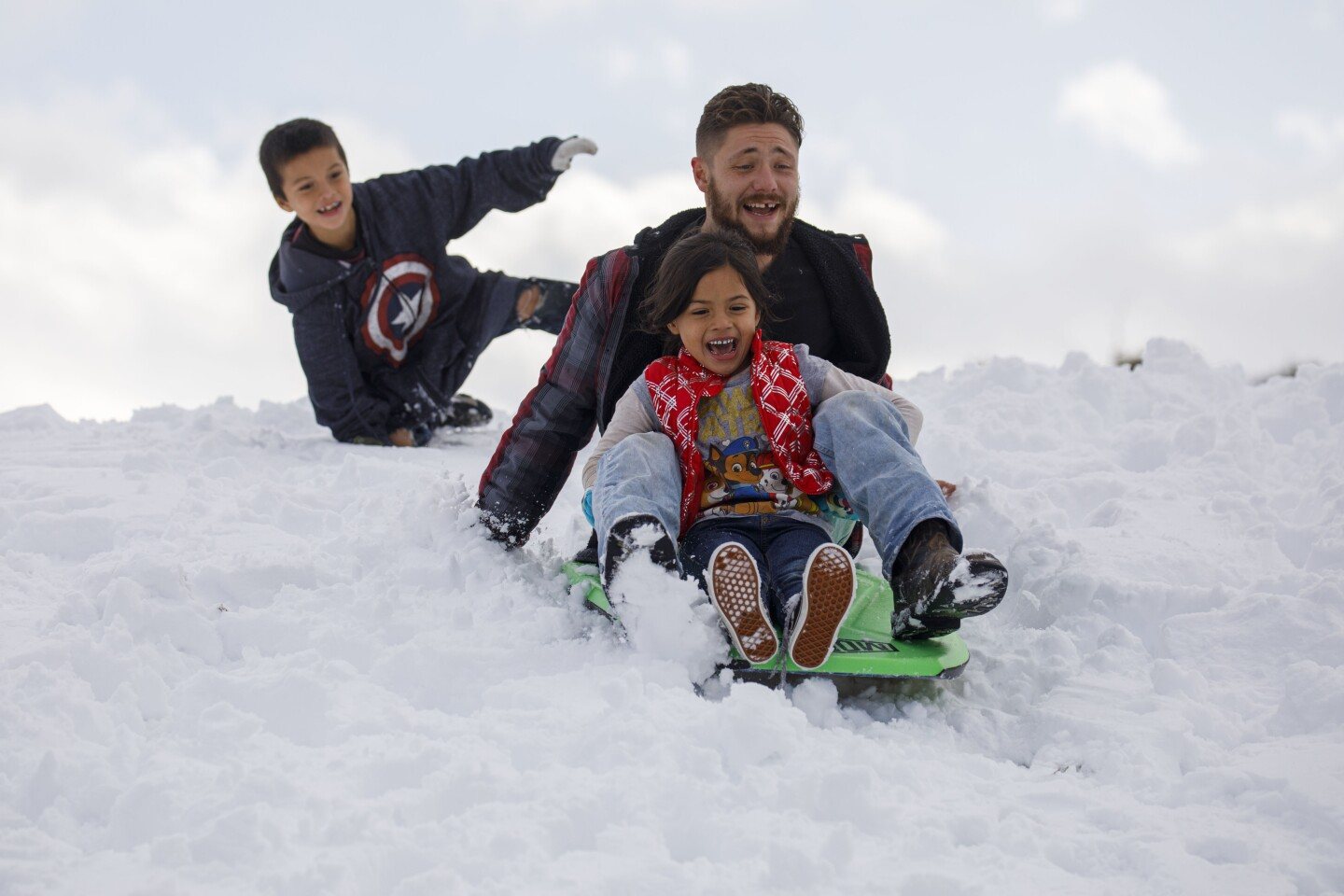 Derek Graham rides a sled with Paige, 6, (in red) and Henry, 7, rear, of Bakersfield as they play in the snow after a winter storm on Friday, November 29, 2019 in Lebec, Calif. The family had planned to go to Mexico but the snow and road closures changed their plans. (Patrick T. Fallon/ For The Los Angeles Times)