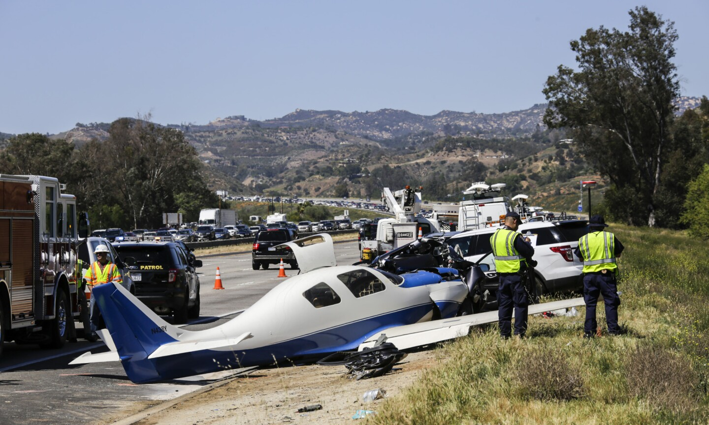 CHP investigators gather at at the site of a small plane that slammed into a car on Interstate 15 in northern San Diego County on Saturday.