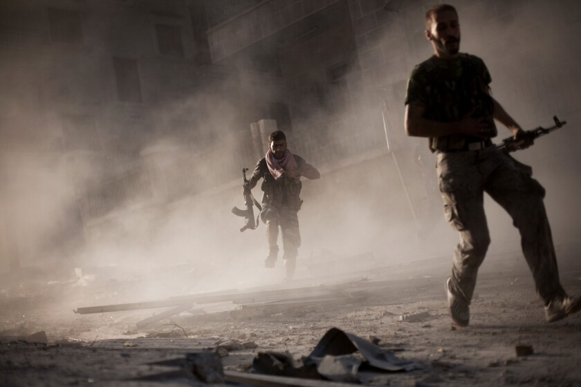 Free Syrian Army fighters run after attacking a Syrian Army tank during fighting in Aleppo, Syria.