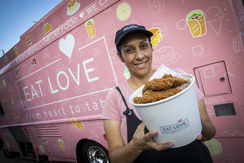 A woman holds the vegan fried chicken bucket from Eat Love in front of a pink food truck.