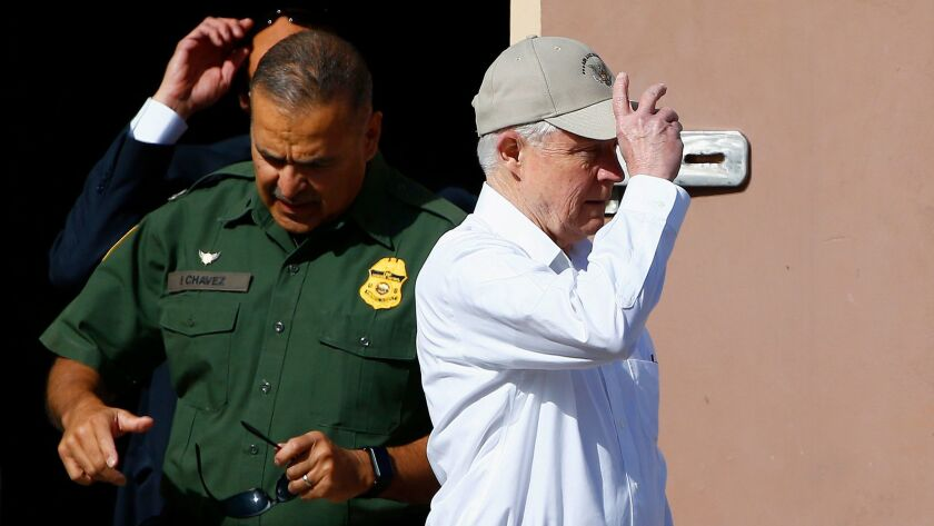 Attorney General Jeff Sessions adjusts his hat as he tours the U.S.-Mexico border with border offici