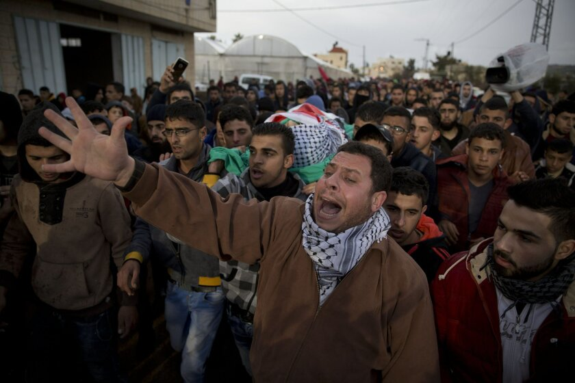Palestinian mourners carry the body of Qusay Abo al-Rub, who was shot and killed when he tried to stab a soldier at a checkpoint, during his funeral, in the West Bank village of Kabatiya, near Jenin, Sunday, Feb. 21, 2016. (AP Photo/Majdi Mohammed)