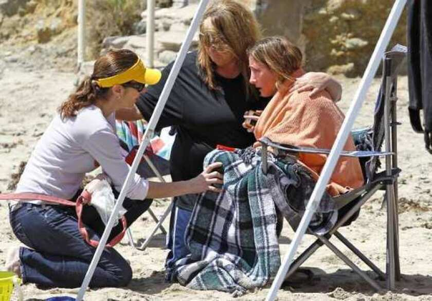 A woman is comforted at the scene where a 51-year-old diver from Orange County was reported missing.