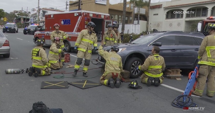 Firefighters on Friday morning work to lift a Subaru Outback off a 74-year-old bicyclist who was struck and pinned under the vehicle.