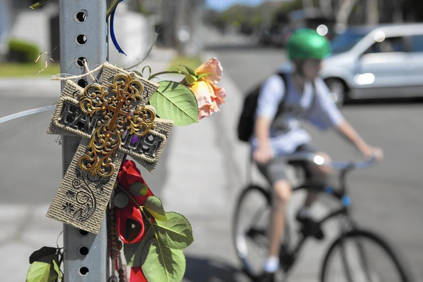 A young bicyclist passes a sidewalk memorial for 8-year-old Brock McCann, who was struck and killed by a trash truck May 25 at the intersection of 15th Street and Michael Place in Newport Beach while riding his bike home from school.