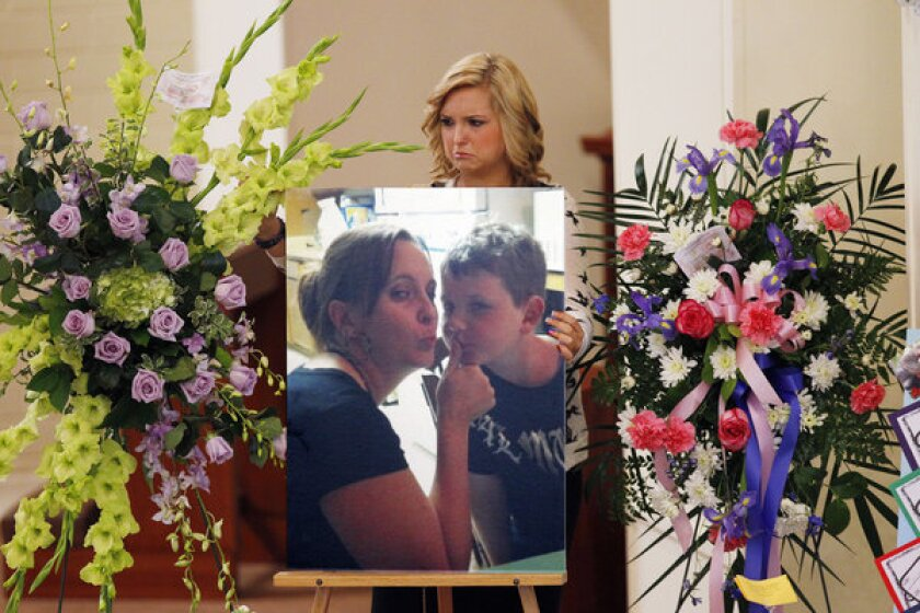 Kidnap victim Hannah Anderson positions a photo of her slain mother, Christina Anderson, and brother, Ethan Anderson, on an easel at an Aug. 24 memorial service.