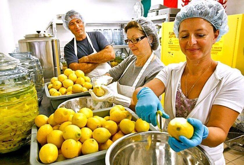 Rossana Zaretti, center, and daughter Manuela Zaretti-Carling, with Manuela's husband, Ventura Limoncello co-owner James Carling, peel lemons for limoncello.