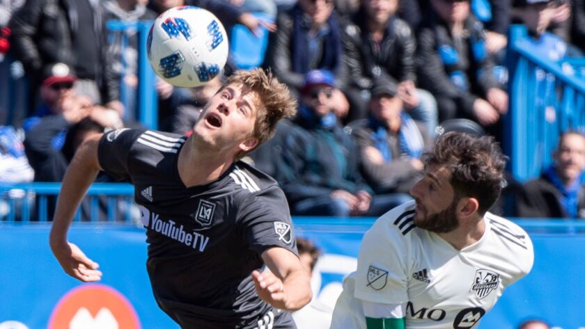 Los Angeles FC defender Walker Zimmerman, left, lunges to knock the ball away from Montreal Impact m