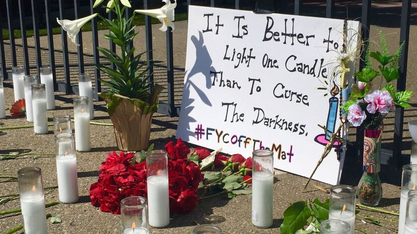 A memorial of candles and flowers honors victims of Tuesday's shooting outside Catholic Charities We