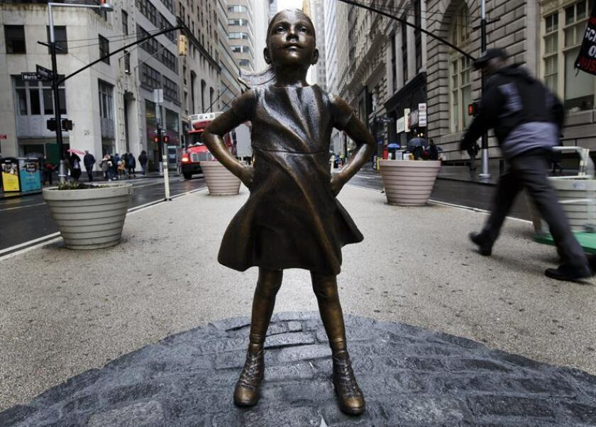 """MIA16 - NUEVA YORK (NY, EE.UU.), 19/04/2018.- fotografía de archivo (27/03/2017) donde aparece la """"Niña sin miedo"""", una estatua de una niña instalada hace un año en actitud desafiante frente al famoso toro de Wall Street en Nueva York. La estatua de bronce que fue montada por sorpresa el 7 de marzo de 2017, en la víspera del Día de la Mujer, en una instalación financiada por una empresa privada y sin contar con los permisos correspondientes, será trasladada a una nueva ubicación permanente, esta vez ante la sede de la Bolsa de Nueva York, informaron hoy fuentes oficiales. EFE/Archivo/Justin Lane"""