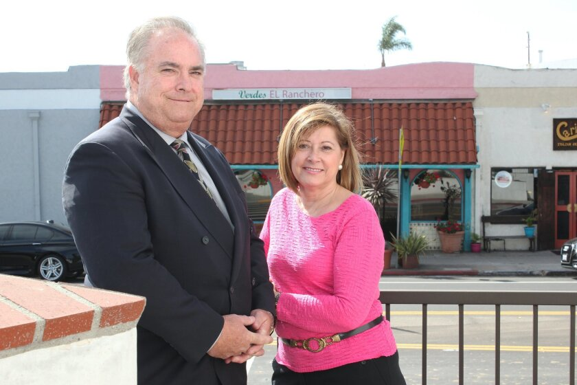 Lori and David Bolton pose in front of the building on La Jolla Boulevard where they plan to open an 18/8 men's salon franchise, directly across from the Mexican eatery where they had their first date, more than three decades ago.