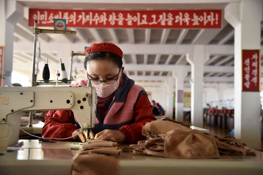 A worker at the Songyo Knitwear Factory in Pyongyang produces masks