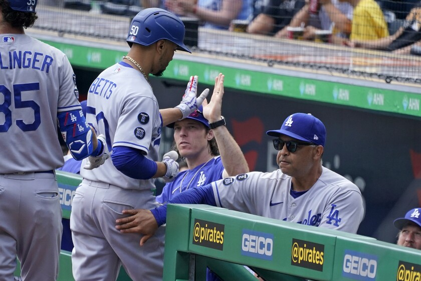 Mookie Betts of the Dodgers is greeted at the dugout Thursday after hitting a home run to lead off against the Pirates.