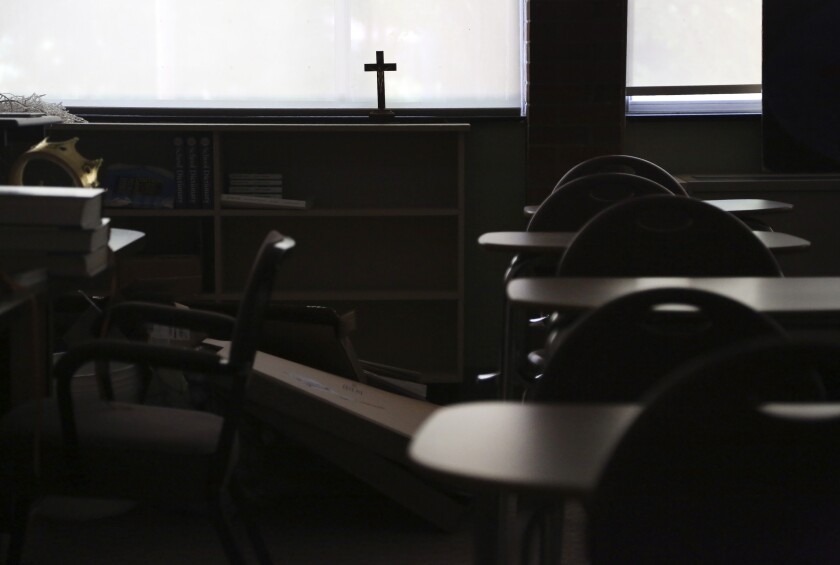 A cross sits in the window of an empty classroom at Quigley Catholic High School in Baden, Pa., Monday, June 8, 2020. Pittsburgh Bishop David Zubik recently announced the school's closure, saying the decision was based on declining enrollment, unsustainable cost projections and insufficient funds to assure its long-term viability. (AP Photo/Jessie Wardarski)