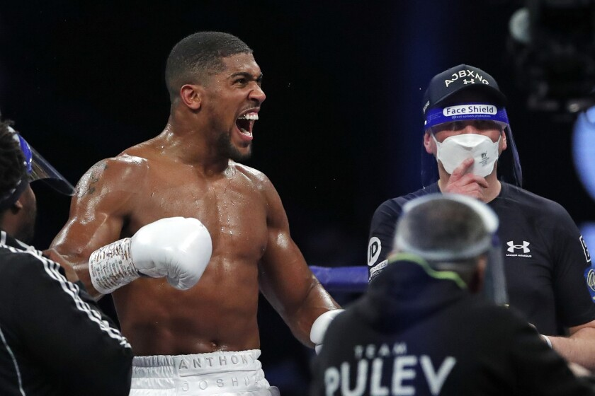 FILE - In this Dec. 12, 2020 file photo, heavyweight boxing champion Britain's Anthony Joshua celebrates after beating challenger Bulgaria's Kubrat Pulev in their title fight at Wembley Arena in London. Anthony Joshua faces Oleksandr Usyk in the second defense of his second spell as world heavyweight champion on Saturday Sept. 25, 2021 in front of 60,000 fans at Tottenham Hotspur Stadium. (Andrew Couldridge/Pool Photo via AP, File)