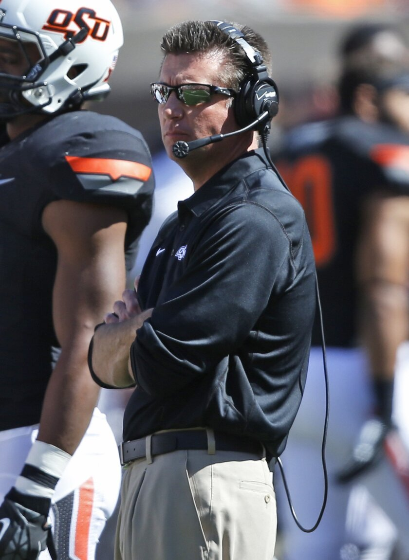 Oklahoma State head coach Mike Gundy watches from the sidelines in the fourth quarter of an NCAA college football game against Iowa State in Stillwater, Okla., Saturday, Oct. 4, 2014. Oklahoma State won 37-20. (AP Photo/Sue Ogrocki)