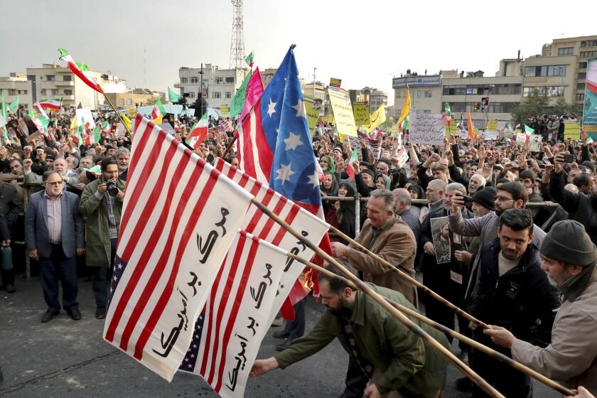 Demonstrators burn representations of the U.S. flag  in Tehran.