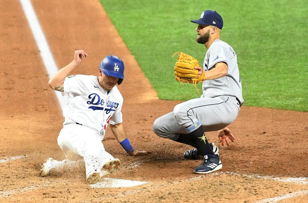 Dodgers baserunner Austin Barnes scores in front of Rays pitcher Nick Anderson on a wild pitch.