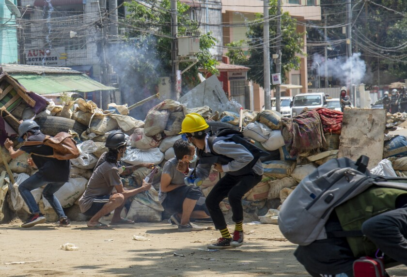 Armed riot policemen charge after firing teargas a rubber bullets as anti-coup protesters abandon their makeshift barricades and run in Yangon, Myanmar Tuesday, March 16, 2021. (AP Photo)
