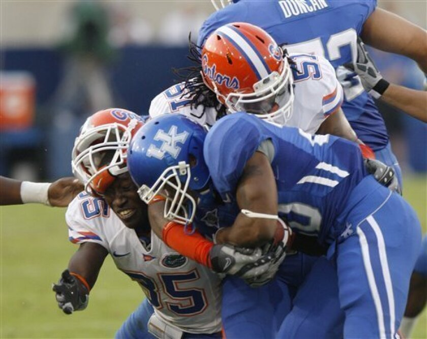 Kentucky running back Derrick Locke is tackled by Florida linebacker Lerentee McCray, left, and Florida linebacker Brandon Spikes as he tries to rush the ball during the first half of their NCAA college football game in Lexington, Ky., Saturday, Sept. 26, 2009. (AP Photo/James Crisp)