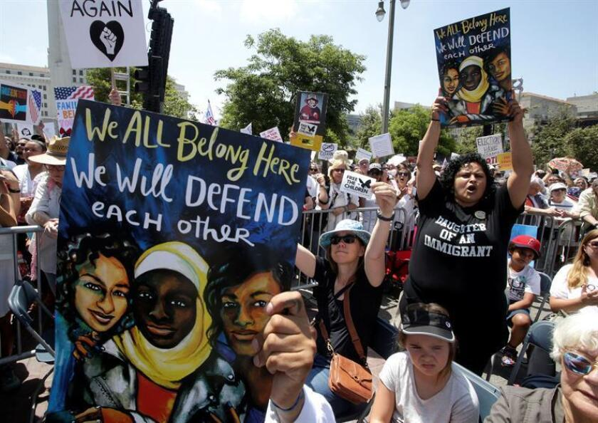 Sugei Ortega-de la Rosa (R) holds a sign that reads 'We All Belong Here. We will Defend each other' as she joined thousands who marched in protest of the immigration policies of US President Donald Trump in Los Angeles, California, USA, 30 June 2018. EFE