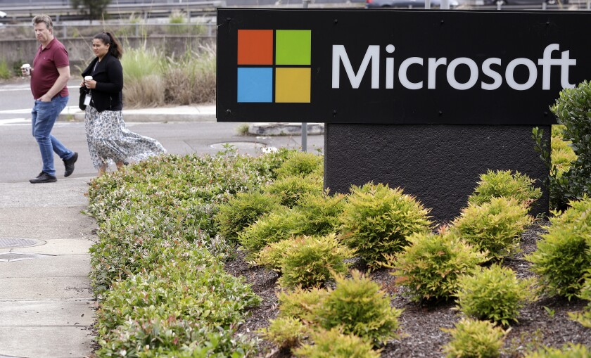 People walk past the Microsoft offices in Sydney, Wednesday, Feb. 3, 2021. Microsoft says it supports Australia's plans to make the biggest digital platforms pay for news and would help small businesses transfer their advertising to Bing if Google quits the country. (AP Photo/Rick Rycroft)