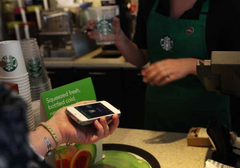 A Starbucks customer uses the Starbucks iPhone app to pay for a coffee at a store in Los Angeles. Starbucks announced a major deal with Square, which will take effect in the fall.
