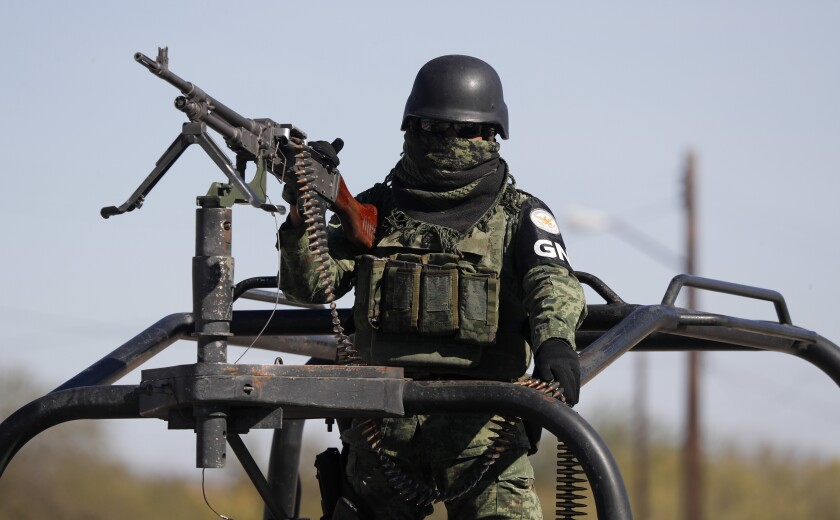 A member of the Mexican security forces stands guard during a visit Coahuila Gov. Miguel Riquelme, in Villa Union, Mexico, Tuesday, Dec. 3, 2019. Mexican security forces fought an hour-long gun gun battle Saturday with suspected cartel gunmen in Villa Union, a town in Coahuila state about an hour's drive southwest of Eagle Pass, Texas, leaving at least 23 people dead. (AP Photo/Eduardo Verdugo)