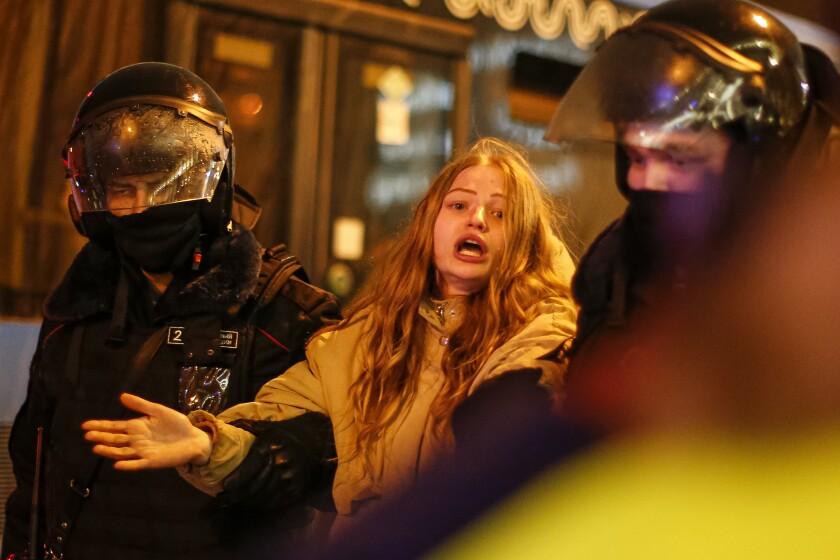 Two officers in riot gear hold the arms of a woman.