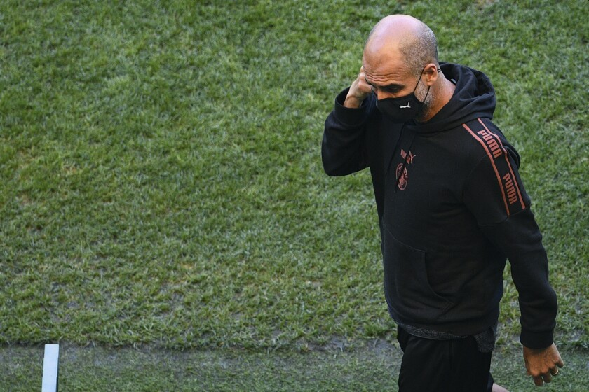 Manchester City's head coach Pep Guardiola walks on the pitch of the Jose Alvalade stadium in Lisbon, Friday Aug. 14, 2020. Manchester City will play Lyon in a Champions League quarterfinals soccer match on Saturday. (Franck Fife/Pool via AP)