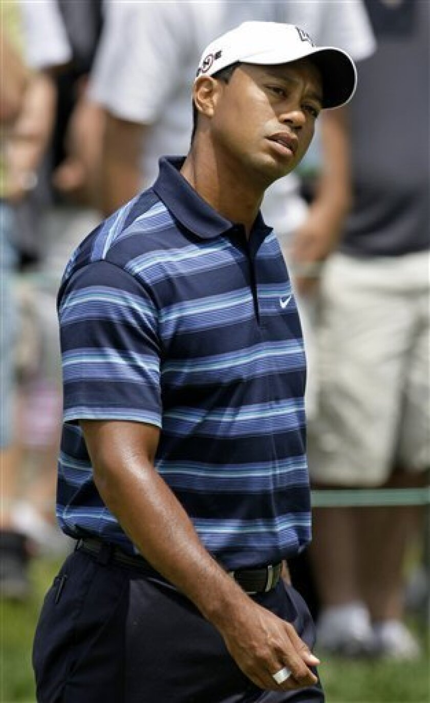 Tiger Woods stretches his neck on the practice green before playing the first round of the Memorial golf tournament at Muirfield Village Golf Club Thursday, June 3, 2010, in Dublin, Ohio. (AP Photo/Tony Dejak)