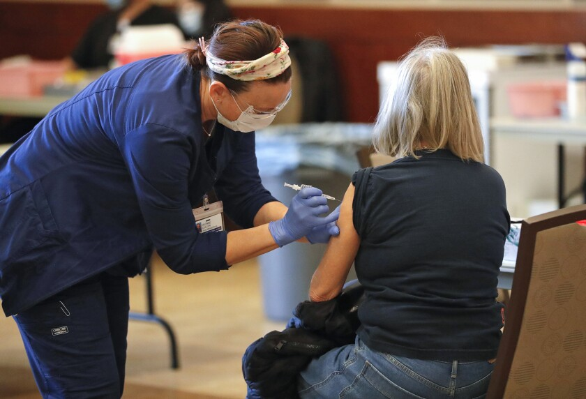 Deonne Cullen, a vocational nurse from Hoag Medical Group, administers the Pfizer vaccine.