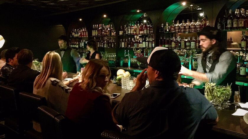 Bartender Chad Lee, right, serves customers on Saturday, Nov. 19, at the newly opened 101 Proof speakeasy inside Urge Gastropub and Whiskey Bank in Oceanside.