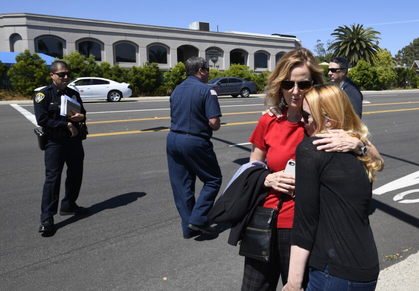Jessica Parks, right, hugs Tina White outside Chabad of Poway synagogue.