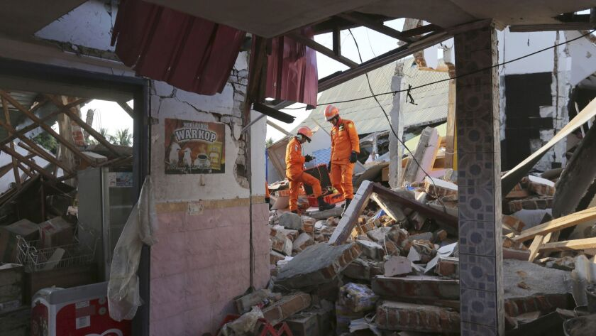 Rescue teams search for victims in the rubble caused by an earthquake in North Lombok, Indonesia, Mo