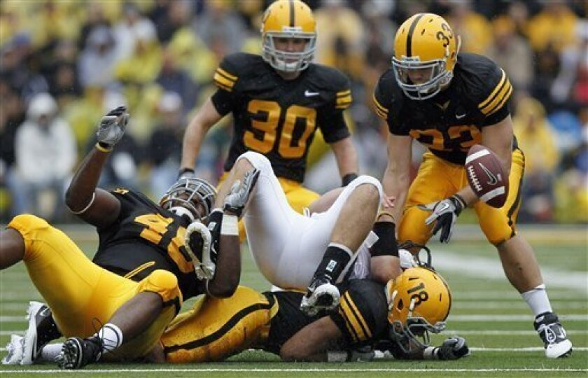 FILE - In this Sept. 25, 2010, file photo, Ball State quarterback Keith Wenning, center, fumbles the ball between Iowa defenders Christian Ballard, left, Micah Hyde (18), Brett Greenwood (30) and Jeff Tarpinian (33) during the first half of an NCAA college football game in Iowa City, Iowa. Iowa's defense is rounding into form as Big Ten play opens this weekend when they host Penn State. The 17th-ranked Hawkeyes lead the nation in total defense after holding Ball State to just 112 yards last Saturday. (AP Photo/Charlie Neibergall, File)